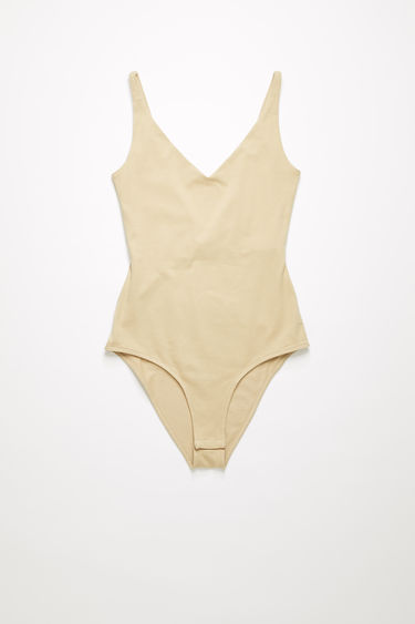 Acne Studios beige sleeveless bodysuit is crafted from stretchy cotton-blend jersey with a deep v-neck, and a scooped back and secured with a press-stud fastening base.