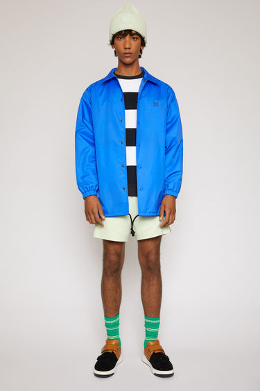 Acne Studios electric blue coach jacket is shaped with a point collar and a drawstring waist and features a face motif print across the back.