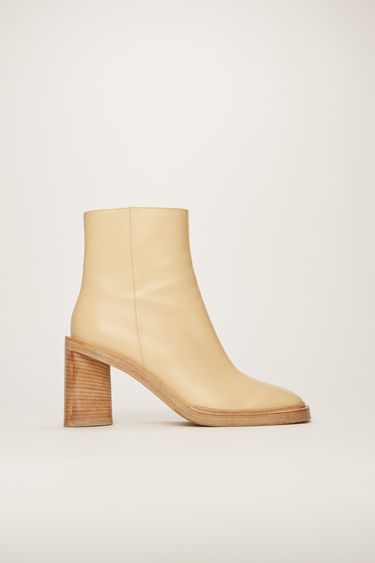 Acne Studios ecru/beige ankle boots are crafted to a squared toe from supple leather and then set on a triangular stacked heel.