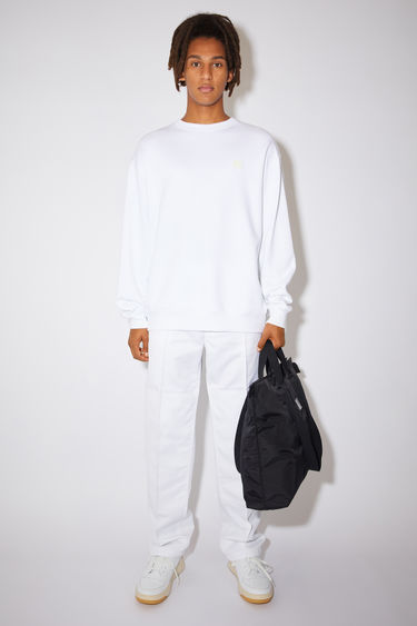 Acne Studios optic white sweatshirt is crafted from midweight loopback jersey to an oversized silhouette with dropped shoulders and accented with a tonal face-embroidered patch on the chest.