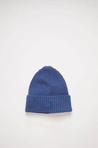 Acne Studios children's dusty blue beanie hat is made from rib knit wool with a face logo patch.