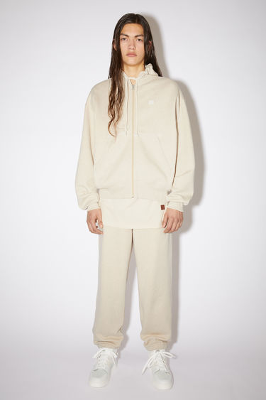 Acne Studios oatmeal melange relaxed hooded sweatshirt is made of organic cotton with a face patch and ribbed details.
