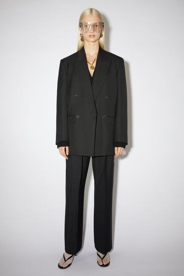 Acne Studios black suit jacket is constructed to a slightly oversized, boxy shape and has lightly padded shoulders, peak lapels and a double-breasted front.