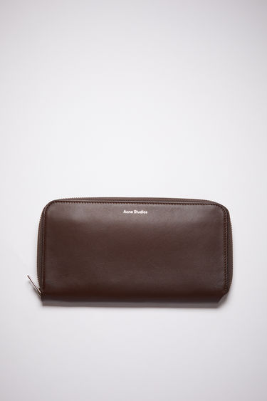 Acne Studios dark brown continental wallet is made of smooth leather with 12 card slots, two bill sleeves, and a zippered compartment for coins.