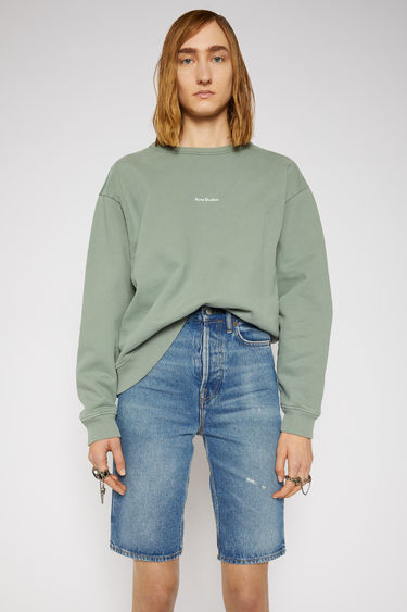 Acne Studios dusty green sweatshirt is made from pigment-dyed jersey that's lightly faded along the seams. It's cut to a relaxed silhouette with dropped shoulders and features a raised logo print on front.