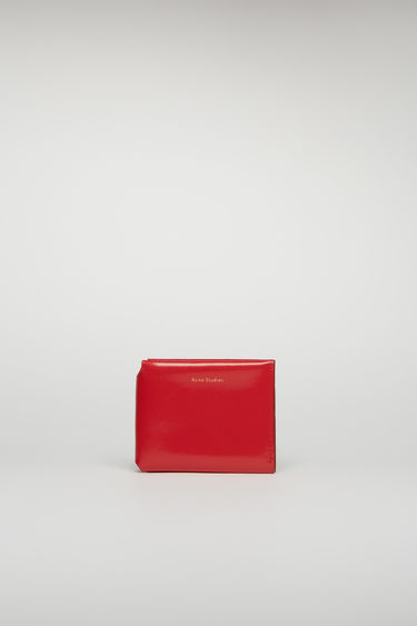Acne Studios red trifold wallet is crafted from high-shine leather and completed with four card slots, a note compartment and a coin pocket.