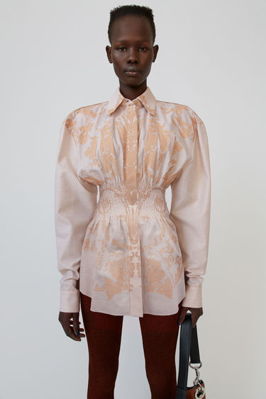 Acne Studios blush pink shirt is shaped with a smocked waistline and emblazoned with the seasonal floral print.
