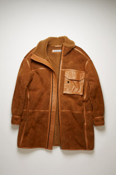 Acne Studios camel brown coat is crafted from soft suede and lined with shearling for optimum warmth. It's adorned with laser-cut designs for a fluid drape and has a wide funnel neck and a leather flap pocket on the chest.