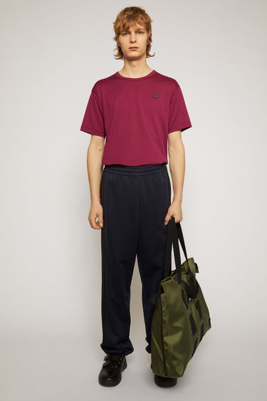 Acne Studios navy blue track pants are crafted from lustrous technical jersey with an elasticated waist and accented with a face-embroidered patch and contrasting side-stripes.