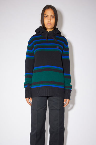 Acne Studios black/blue striped crew neck sweater is made from wool with a face logo patch and ribbed details.