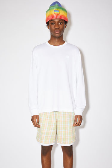 Acne Studios optic white relaxed fit long sleeve t-shirt is made of organic cotton with an embroidered tonal face patch.