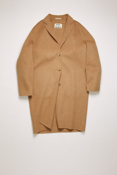 Acne Studios camel melange coat is crafted from double-faced wool to a relaxed silhouette with notch lapels, then fastens with buttons through the front.