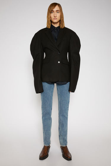 Acne Studios black suit jacket is crafted from wool with voluminous puff sleeves and features a wrap-over single-breasted fastening that cinch the waistline into a feminine silhouette.