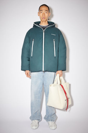 Acne Studios sea green hooded down jacket is made of nylon with a quilted interior and Acne Studios branding at the chest.