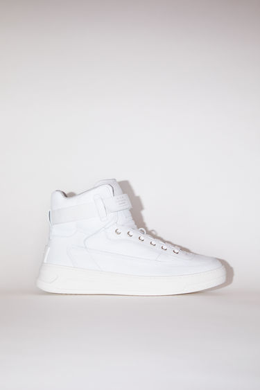 Acne Studios white/optic white lace-up high top sneakers are made of calf leather with a face motif on the back sole.