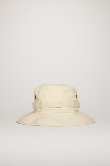 Acne Studios champagne beige bucket hat is crafted with a flat-topped crown and a quilted brim and features metal eyelet vents and a logo-embroidered woven band.