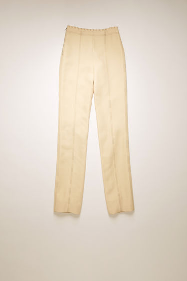 Acne Studios cream beige trousers are cut to a high-rise waist with slim, tapered legs and feature contrast stitching along the waist and seams.
