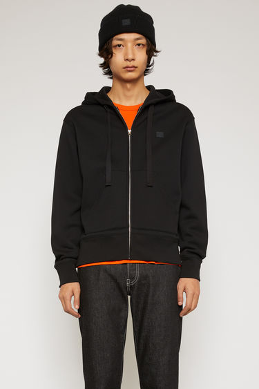 Acne Studios Ferris Zip Face black is a hooded sweatshirt made from midweight brushed fleece and finished with a tonal face patch and a front zip closure.
