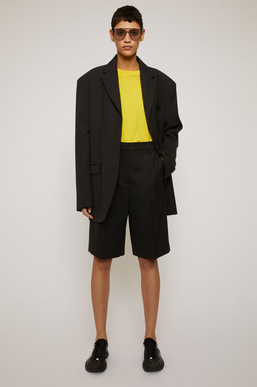 Acne Studios black shorts are crafted from a wool-blend and shaped to loose-fitting, straight legs with pleats on the mid waist.