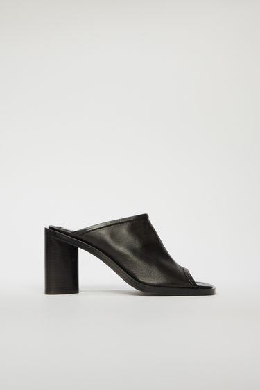Acne Studios black/black mules are crafted from supple leather with an open toe and set on a triangular block heel.