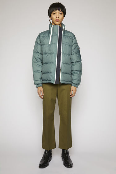 Acne Studios dusty green jacket is made from crinkled nylon shell padded with insulating down and secured with double zip closures and elasticated cuffs and hem.