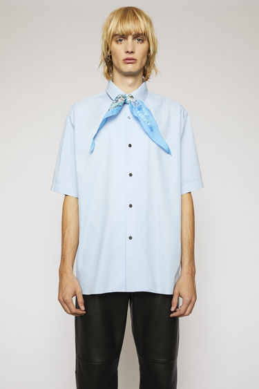 Acne Studios pale blue shirt is crafted to a boxy silhouette from cotton poplin and features a pointed collar and mismatched buttons.