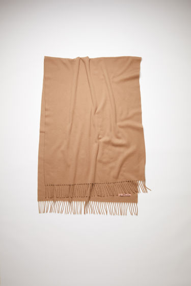 Acne Studios Canada New camel brown scarf is crafted from pure cashmere to a wide dimension with fringed edges and set with a label in one corner.