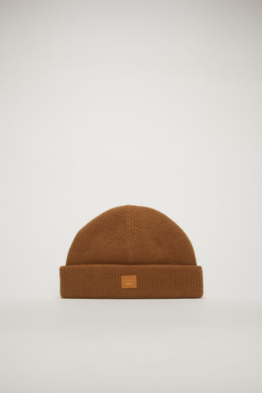 Acne Studios caramel brown beanie is rib-knitted to fit snugly on your head with a turned-up hem and accented with a face-embroidered patch on the front.