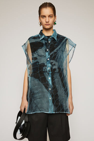 Acne Studios light blue sleeveless blouse is crafted from organza with a subtle sheen finish and features a faintly printed cover of Propaganda Magazine.