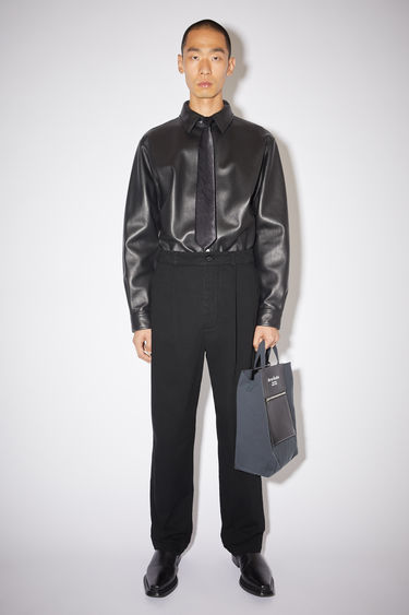 Acne Studios black wide leg trousers are made of cotton with a slight stretch.
