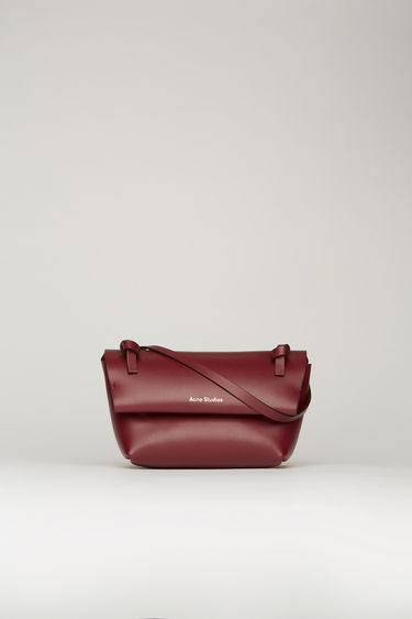 Acne Studios burgundy mini purse crafted from soft-grained leather with a knotted shoulder strap. It has magnetic fastenings that open to reveal a tonal leather lining with a single slip pocket.