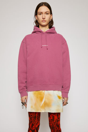 Acne Studios violet pink hooded sweatshirt is made from organic cotton that's lightly faded along the seams. It's cut to a relaxed silhouette with dropped shoulders and ribbed edges and features a raised logo print on front.