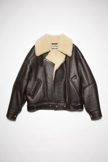 Acne Studios dark brown/ beige shearling jacket is crafted with soft lamb shearling and framed with contrasting leather trims.