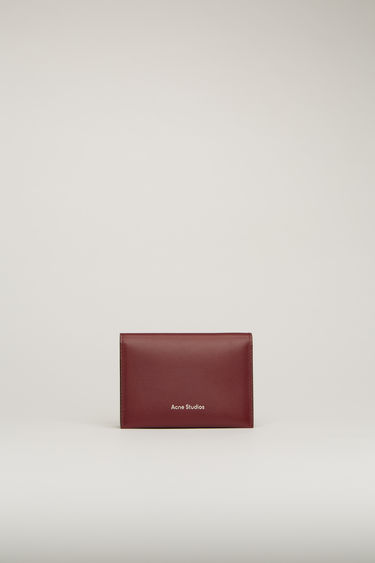 Acne Studios burgundy cardholder is crafted from grained leather to a folded construction and features four card slots and a silver stamped logo on front.