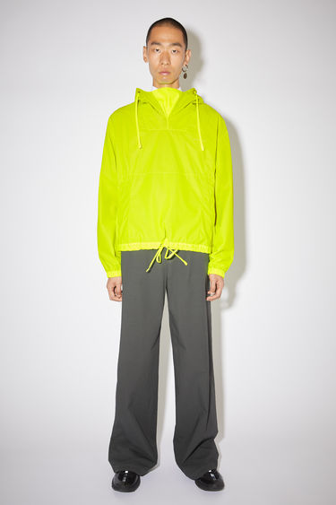 Acne Studios neon yellow hooded anorak jacket has a printed logo and relaxed fit.