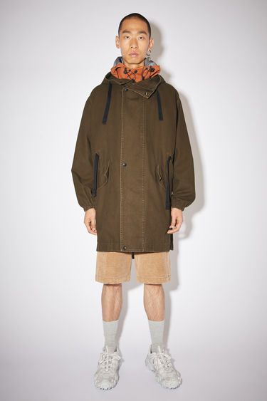 Acne Studios cedar green oversized fishtail parka is made of cotton with thick black drawstrings.