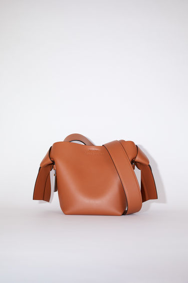 Acne Studios almond brown small bag features twisted knots inspired by traditional Japanese obi sashes. It has a debossed logo and snap button closure, which opens to reveal a zipper compartment for storing small essentials.