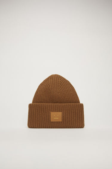 Acne Studios caramel brown beanie is rib-knitted from soft wool and accented with a face-embroidered patch on the front.
