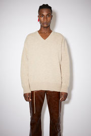 Acne Studios oat beige v-neck sweater is made of a wool and recycled cashmere blend with a relaxed fit.