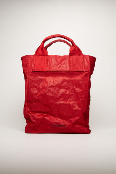 Acne Studios dark red tote bag is made from malleable cotton and nylon blend to create a crumpled, boxy silhouette. It features a top handle, adjustable shoulder strap and a logo print across the front.