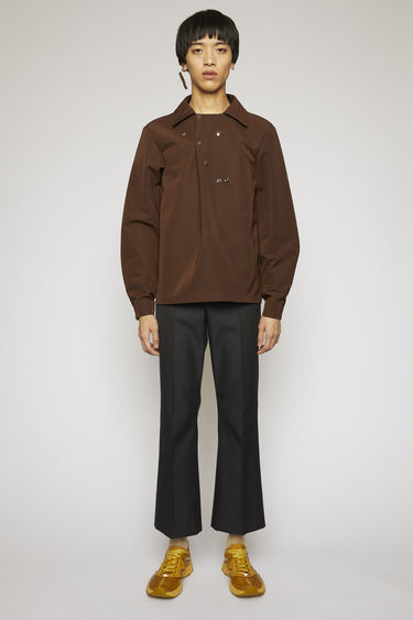 Acne Studios coffee brown shirt is crafted from a technical polyester twill with a spread collar and accented with silver-tone metal hardwares.