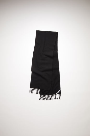 Acne Studios black scarf is crafted from soft wool that's brushed on one side and features a logo label above the fringed edges.