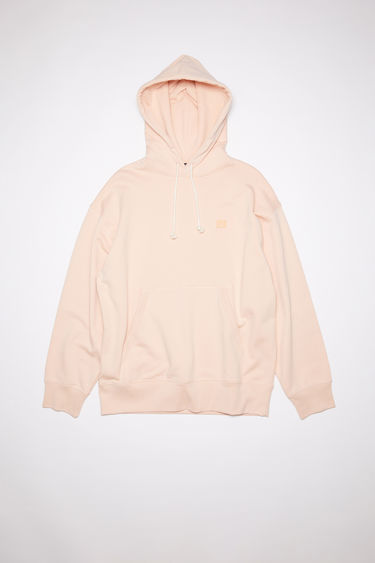 Acne Studios powder pink oversized hooded sweatshirt is made of organic cotton with a face patch and ribbed details.