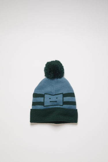 Acne Studios forest green/mineral blue beanie features jacquard stripes and the house's signature face motif. It's adorned with a pom-pom and finished with a ribbed turn-up for a snug fit.