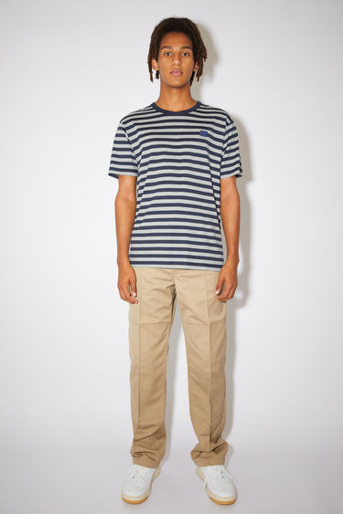 Acne Studios navy striped t-shirt is made from organic cotton with a crew neck, relaxed fit, and a face logo patch.