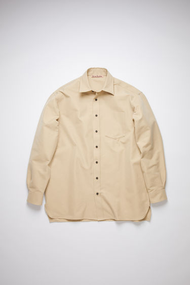 Acne Studios warm beige oversized shirt is made of a matte cotton blend with a relaxed fit.