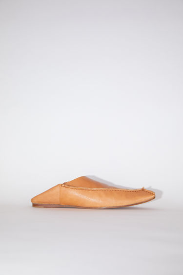 Acne Studios wheat beige are flat slip-on shoes made of leather, inspired by Moroccan babouche slippers.