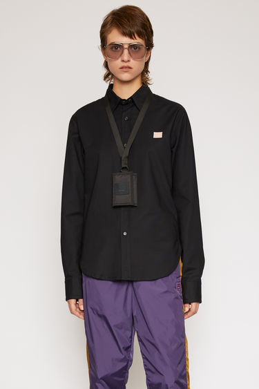 Acne Studios black shirt is shaped to a slim silhouette with a curved hem and accented with a light pink face patch on the chest.