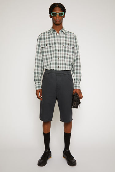 Acne Studios black Acne Studios black shorts are made from brushed cotton jersey that's garment-dyed to create light fading at the seams. They're cut in a straight shape that drapes loosely over the leg have an elasticated drawstring waistband and a classic five-pocket design.