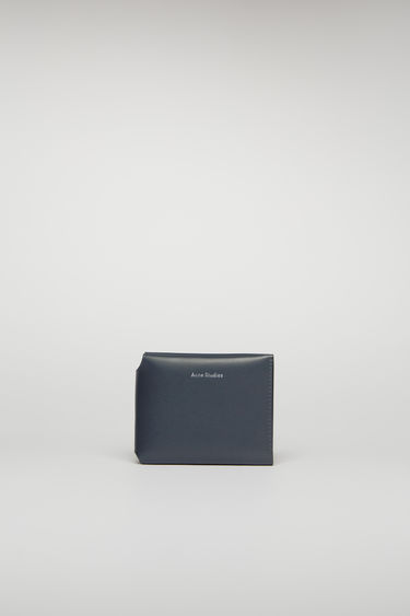 Acne Studios dark blue card wallet unfolds in three ways to reveal an internal coin pocket, four card slots and a slip pocket for notes.